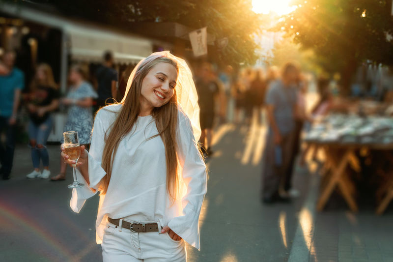 Full length of beautiful young woman drinking glass