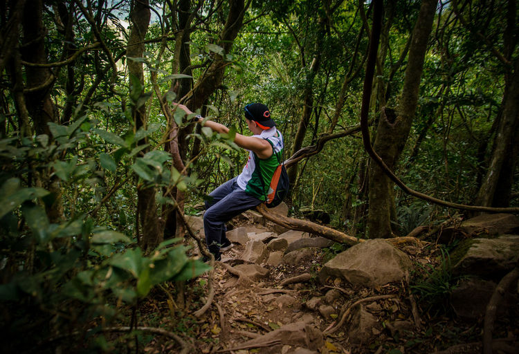 Downhill Adventure Batangas Casual Clothing Day Forest Full Length Growth Holding Land Leisure Activity Lifestyles Men Mountain Climbing Nature One Person Outdoors Plant Rainforest Real People Tree WoodLand Young Adult