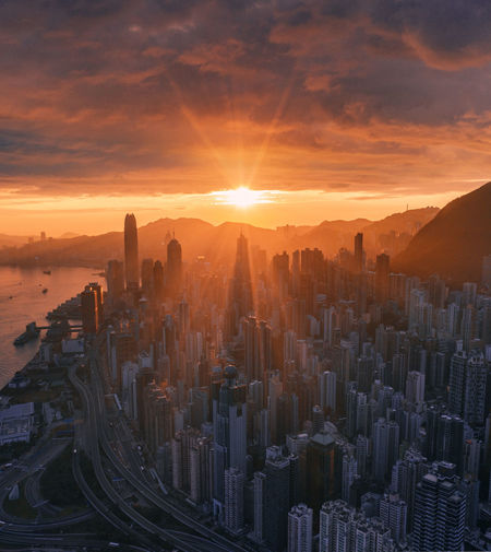 Aerial view of central district in hong kong against sky during sunrise