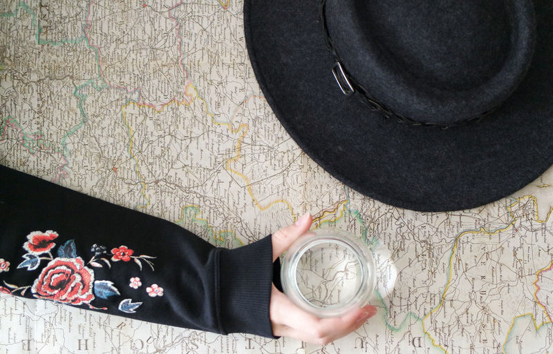 Directly above shot of woman holding glass by hat on map