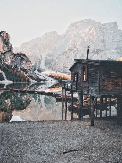Stilt house by lake against mountain