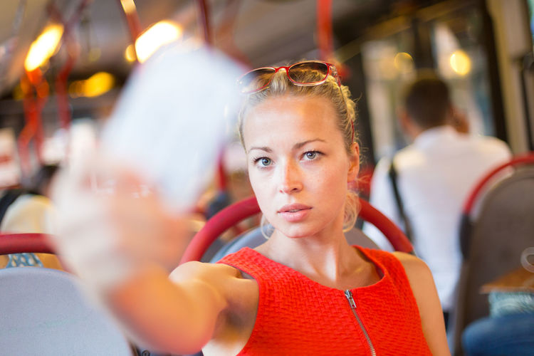 Portrait of beautiful woman taking selfie sitting at bus