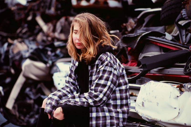 Sad young woman sitting alone in an auto salvage yard