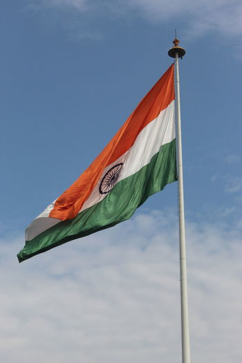 Low angle view of indian flag waving against sky
