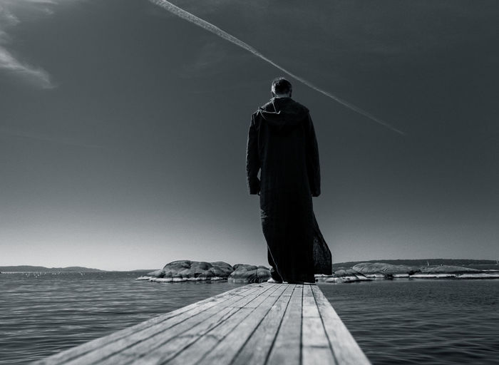 Rear view of man standing by sea on jetty