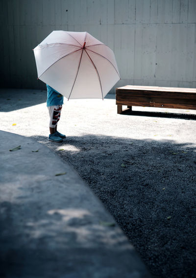 Low section of woman with umbrella walking on footpath