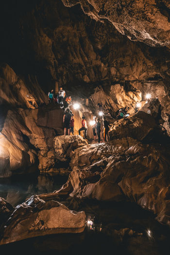 People by illuminated rock formation in cave