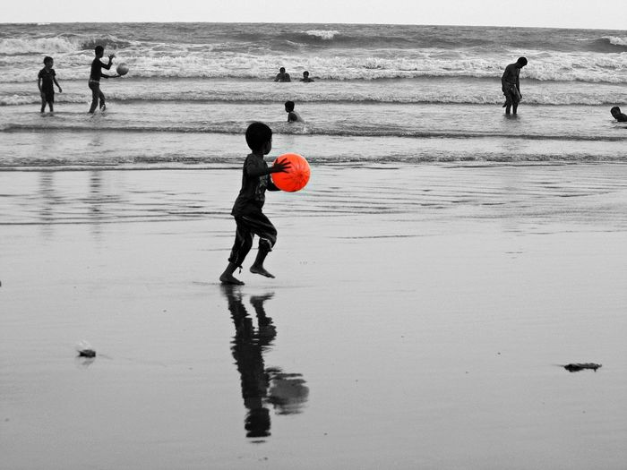 Boy playing with red ball while walking on sea shore