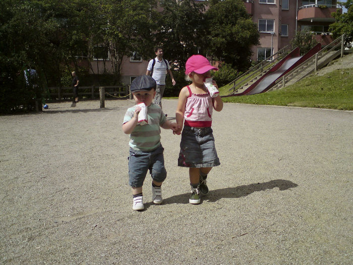 Two young siblings holding hands and drinking soda at the playground. Child Childhood Family Full Length Outdoors Positive Emotion Sibling Sister Togetherness Two People