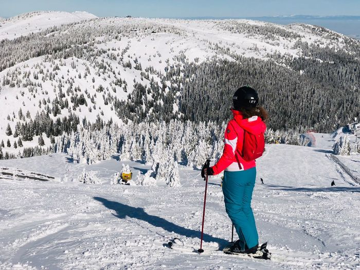 Woman skier on the slope with view of snowcapped mountains ahead on a day with clear blue sky Woman Adult Trees Blue Sky Coniferous Tree Pine Tree Forest Ski Resort  Resort Slope Skier Snow Cold Temperature Winter Full Length One Person Nature Mountain Mountain Range Sport Winter Sport Skiing Clothing Warm Clothing Beauty In Nature Nature Vacations Day Scenics - Nature Ski-wear