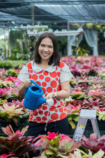 Portrait of a smiling young woman standing in greenhouse