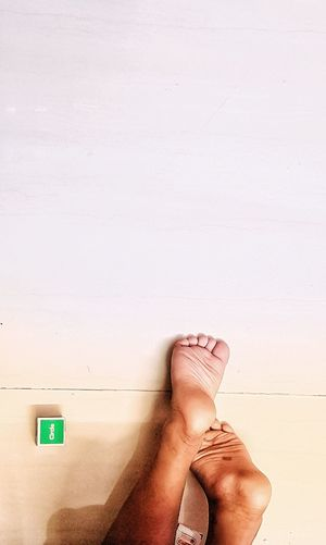 Low Section Of Man With Feet Up Against Wall