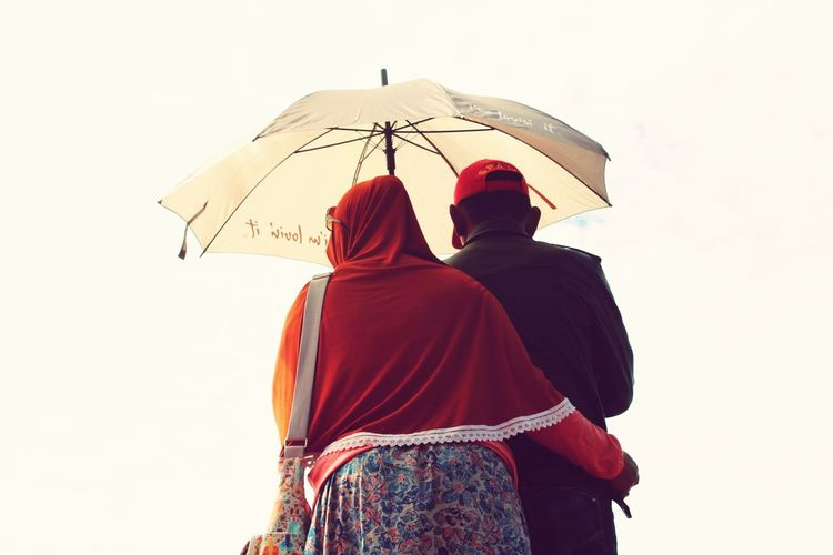 Rear View Of Couple Holding Umbrella Against Sky