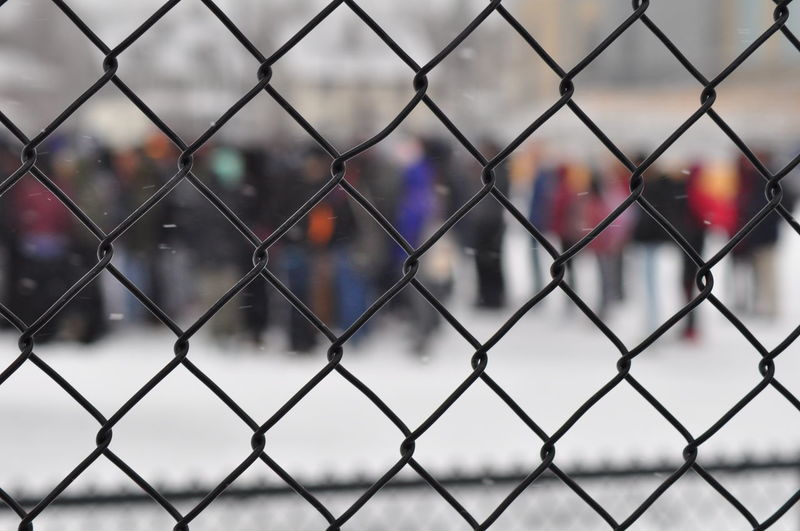 People Seen Through Chainlink Fence During Winter