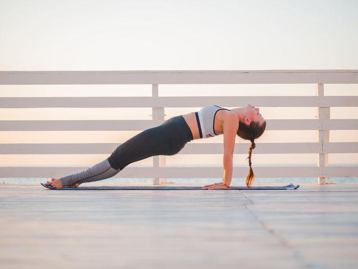 Full Length Of Woman Doing Yoga On Promenade Against Clear Sky During Sunrise