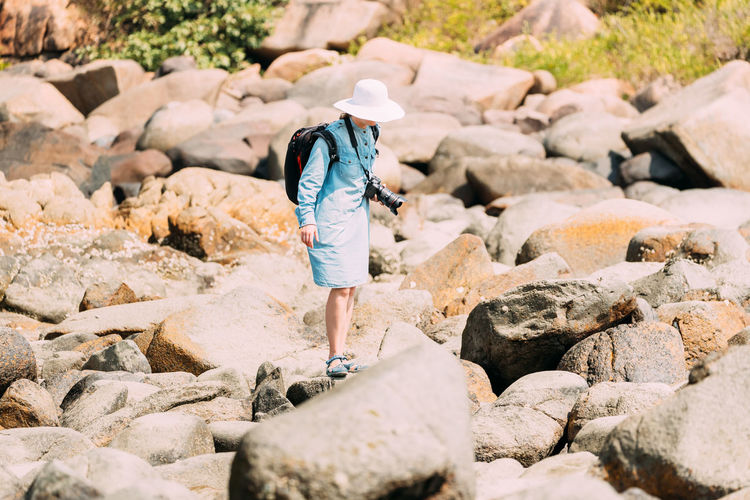 Rear view of woman walking on rocks