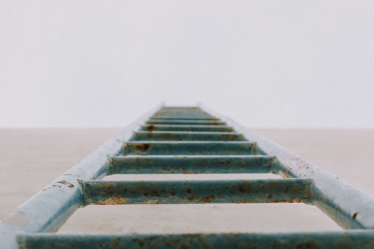 Close-up of ladder against sky