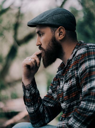 Side view of bearded young man looking away