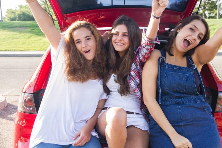 Portrait of happy female friends sitting in car