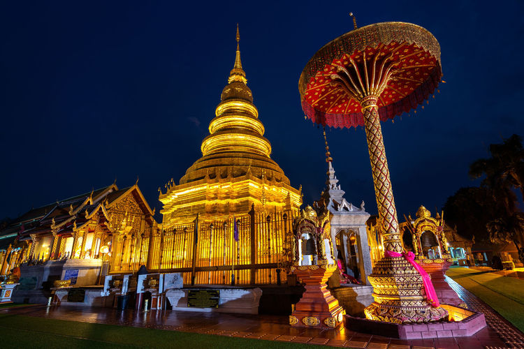 Wat Phra That Hariphunchai temple in Lamphun, Thailand. Night Built Structure Architecture Sky Belief Religion Illuminated Place Of Worship Building Building Exterior Spirituality Nature Travel Destinations Outdoors Amusement Park Tourism No People Blurred Motion