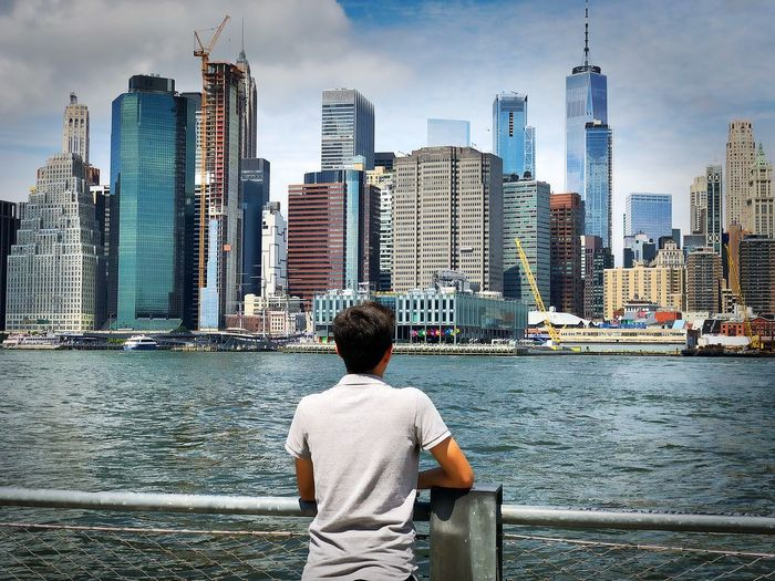 Rear view of teenage boy looking at river against skyscrapers in city
