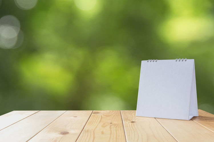 Close-up of blank white spiral notebook on wooden table