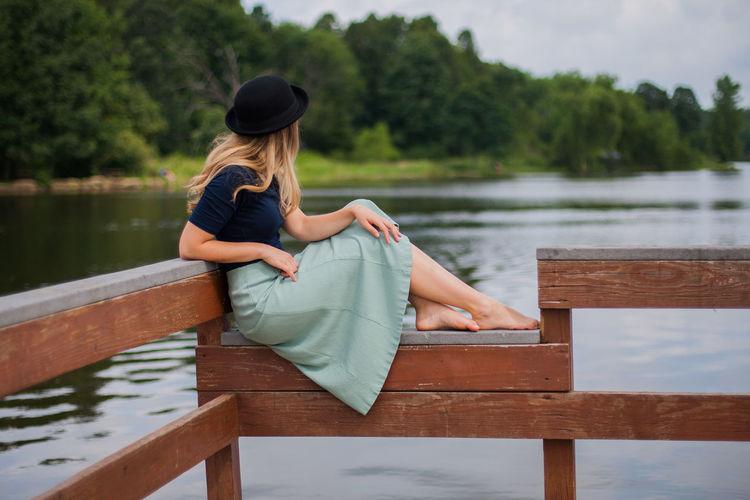 Woman Wearing Skirt Looking At Lake While Sitting On Railing