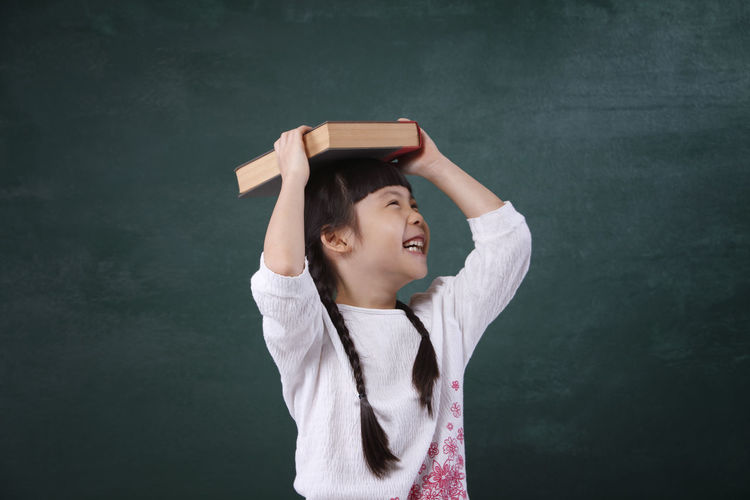 Cheerful girl holding book on head while standing by blackboard