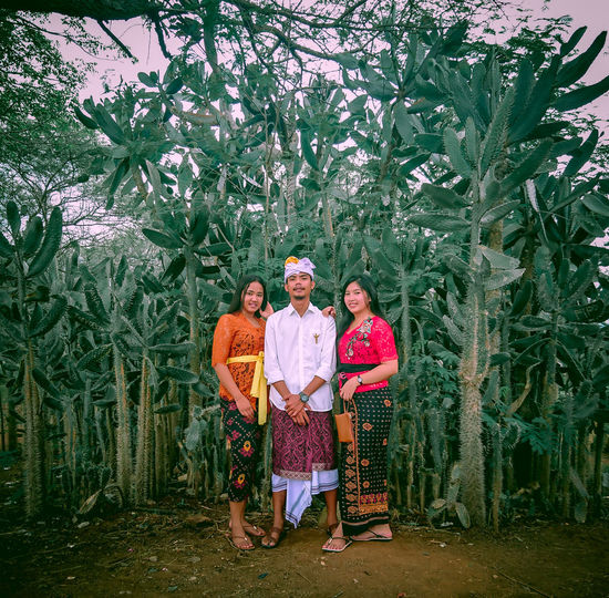 Full length portrait of friends wearing traditional clothing while standing on agricultural field