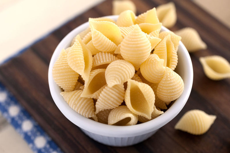 Conchiglie Pasta. Conchiglie Pasta Italian Pasta Natural Light Blue Napkin Bowl Carbohydrates Close Up Conchiglie Cutting Board Dry Pasta Food Food And Drink Italian Food No People Nutrition Pasta Still Life Studio Photography Wooden Background