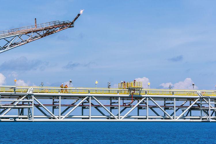 Cranes on pier against sky