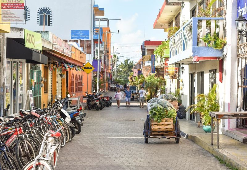 Streets of Mexican town Isla Mujeres Architecture Beauty Bikes Bright Building Exterior Built Structure City Colorful Day Explore Mexican Village No People Outdoors Quaint  Sky Tourism Travel Vacation Vacations Vegetable Cart