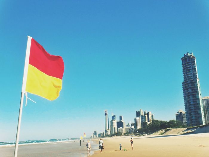 Red And Yellow Striped Flag At Beach Against Clear Sky