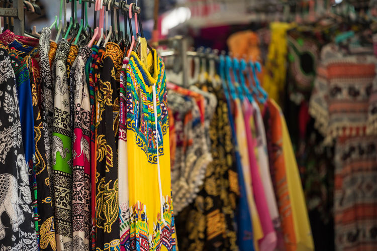 Multi colored clothes hanging in store for sale at market