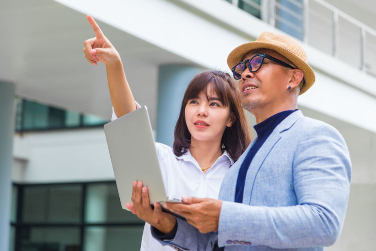 Cheerful Business People Holding Laptop While Standing Outdoors