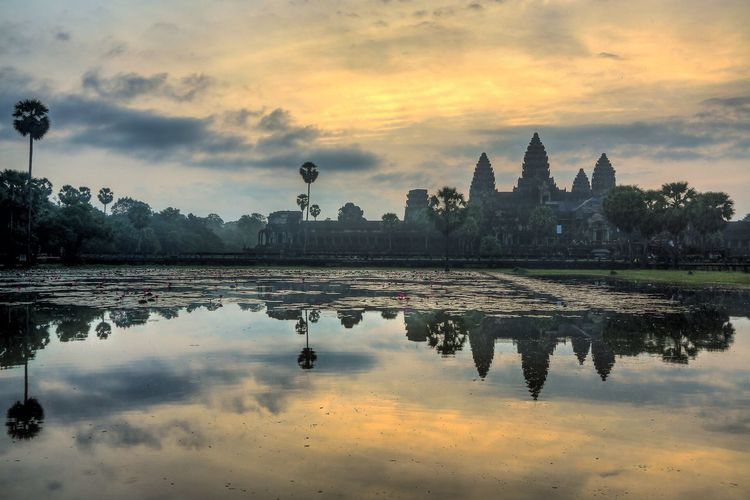 Reflection Of Angkor Wat In Lake At Sunset
