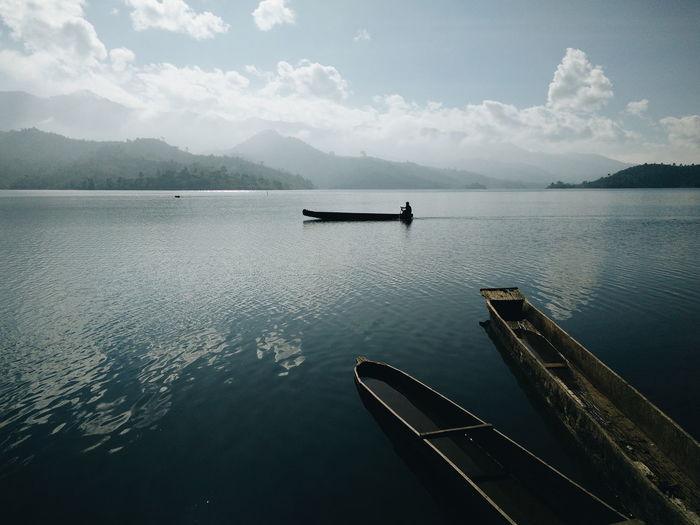 Boat In Calm Sea Against Mountain Range