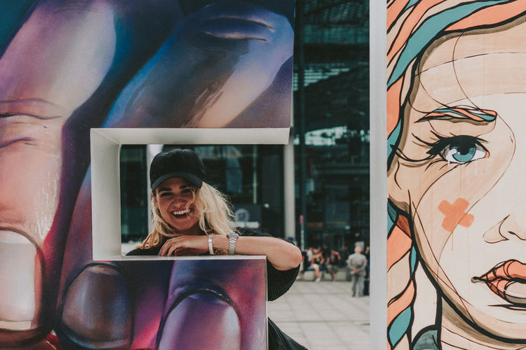 Portrait of smiling young woman with graffiti wall