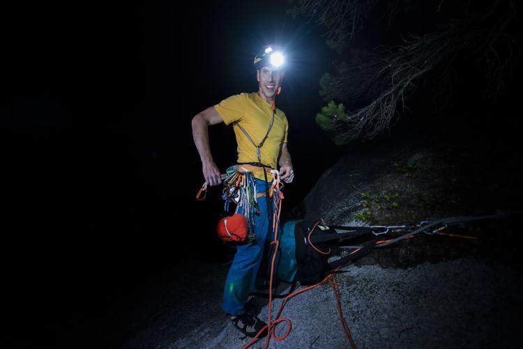 Man standing against illuminated wall at night
