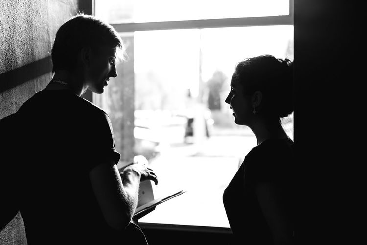 Silhouette of man and woman looking through window