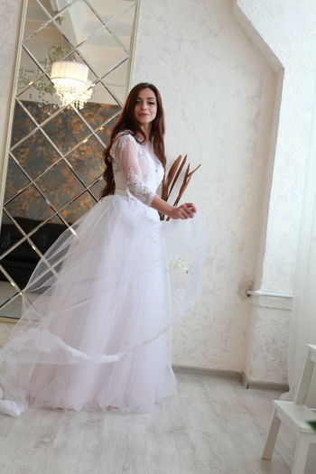 One Person Women Newlywed Wedding Bride Adult Emotion Young Adult Full Length Looking At Camera Smiling Standing Wedding Dress Portrait Fashion Indoors  Event Happiness Celebration Beautiful Woman Hairstyle Contemplation Teenager