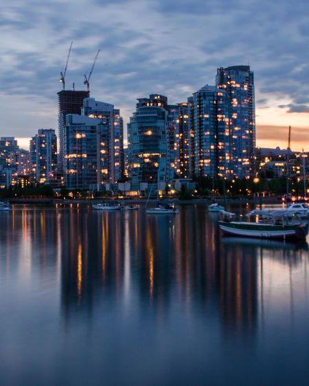 Illuminated Buildings By City Against Sky At Dusk