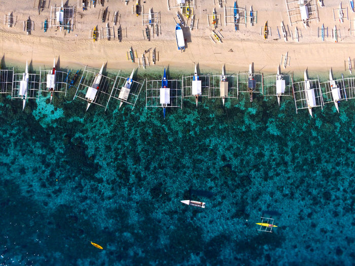High angle view of boats moored at beach and sea