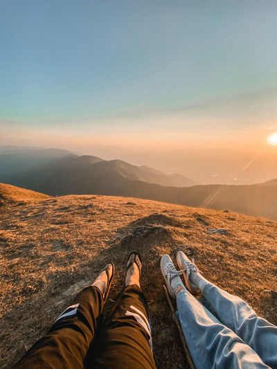 Low section of people sitting on mountain against sky during sunset