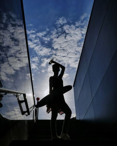 Low angle view of silhouette woman holding skateboard while standing against sky