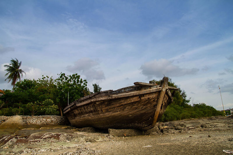 Abandoned boat on shore against sky