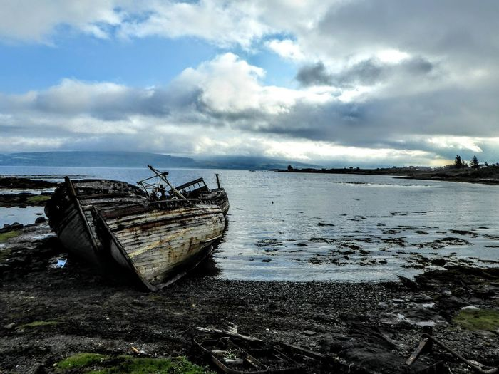 Abandoned boat on beach against sky