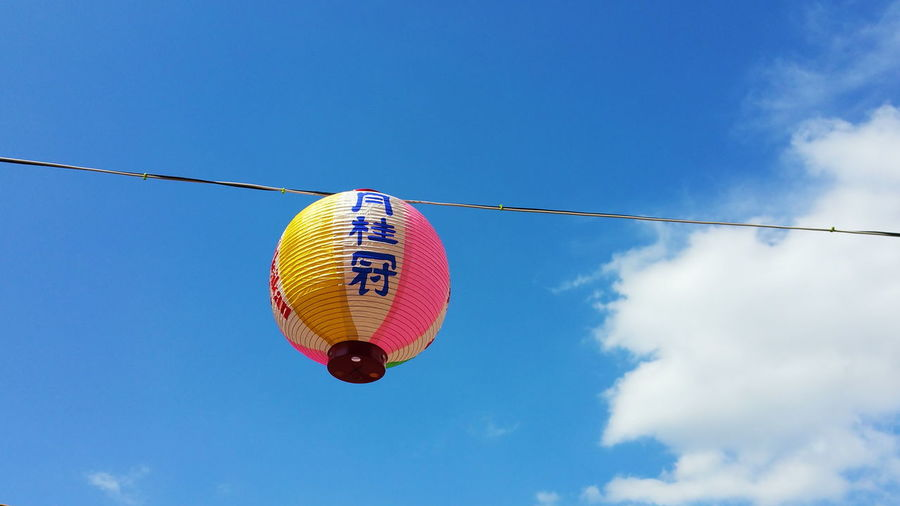 Low angle view of lantern against blue sky