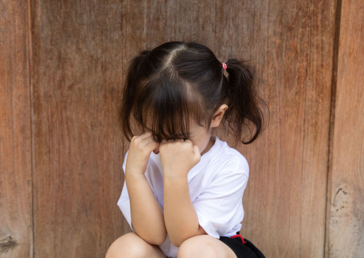 Girl crying while sitting against wooden door