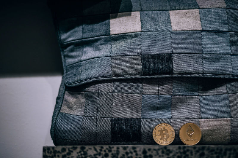 Close-Up Of Coins By Bag On Table